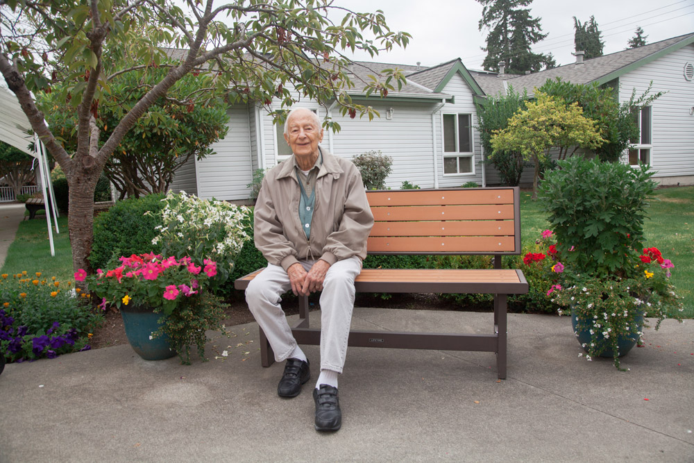 Image description: smiling man sitting on bench at Foss Home and Village Coutyard